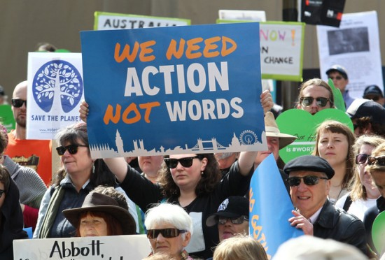 "Image of woman in a crowd holding a sign that reads ""we need action not words""."