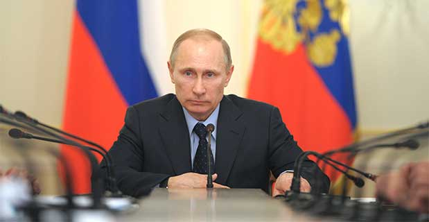 Photo of Vladimir Putin seated at table in front of flags.