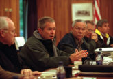 Photograph of George Bush sitting at a table with advisors including Dick Cheney and Colin Powell surrounding him.