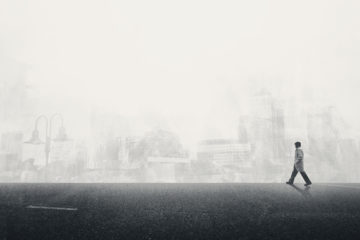 Man walking along in fog against backdrop of a cityscape.